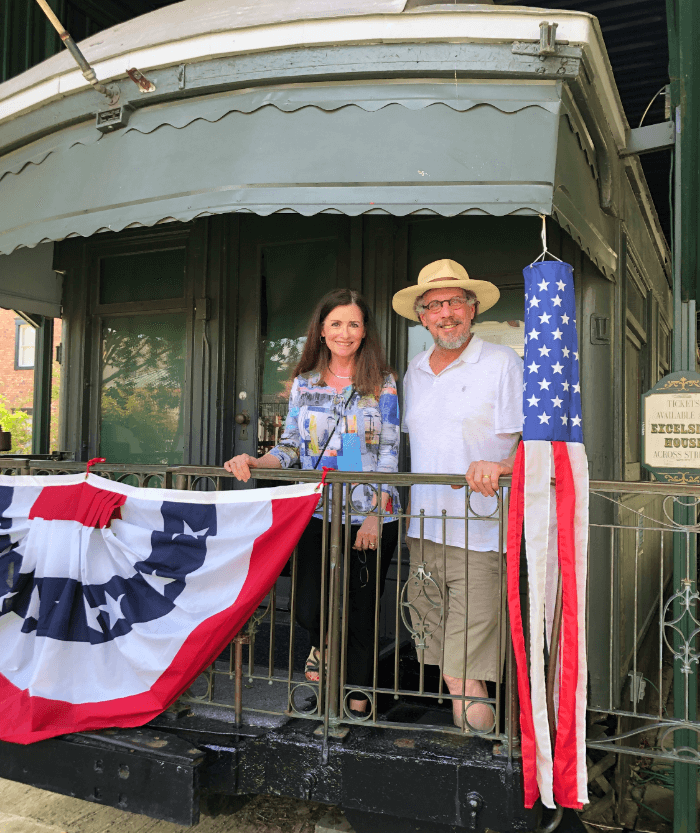 Woman and a man in a straw hat posing on the back of a train decorated with red, white, and blue bunting