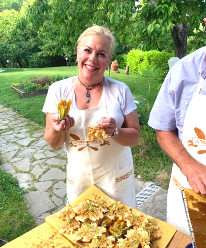 Blonde woman in a white blouse smiling and holding fried zucchini flowers