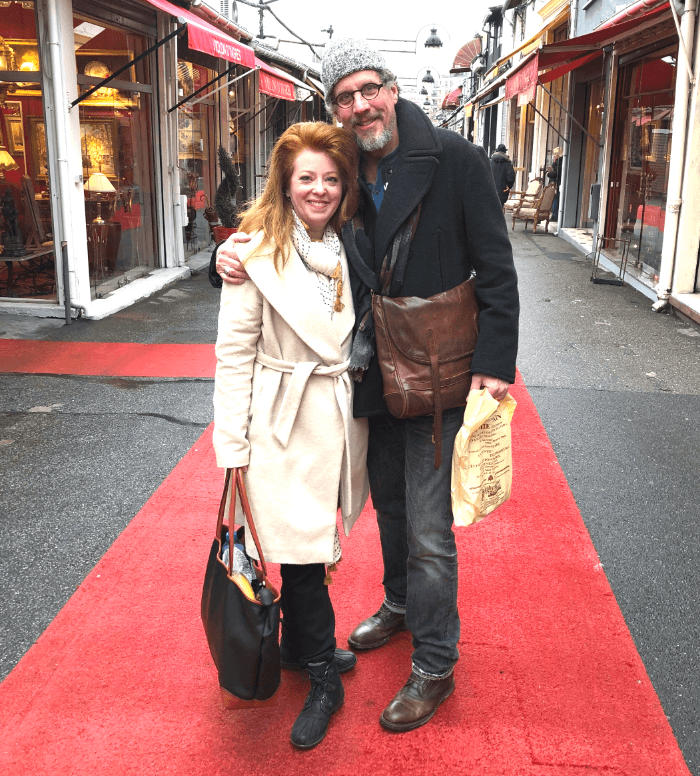 Woman in a white coat and man with a ski cap on standing on a red carpet at the Paris Flea Market