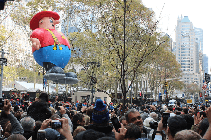a farmer shaped parade balloon floating above a crowd of people