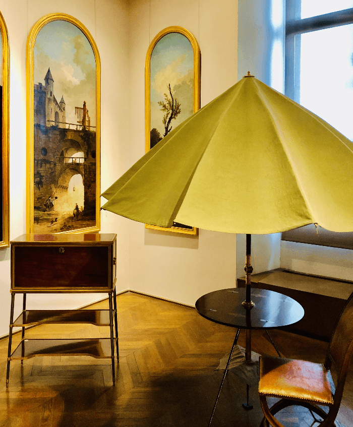 a green umbrella over a small table and chair at the Decorative Arts Museum