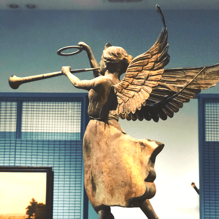 a metal weather vane in the shape of an angel