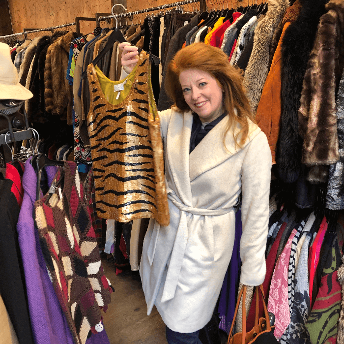a woman in a white coat holding up a sequined tiger print vest in a clothing shop