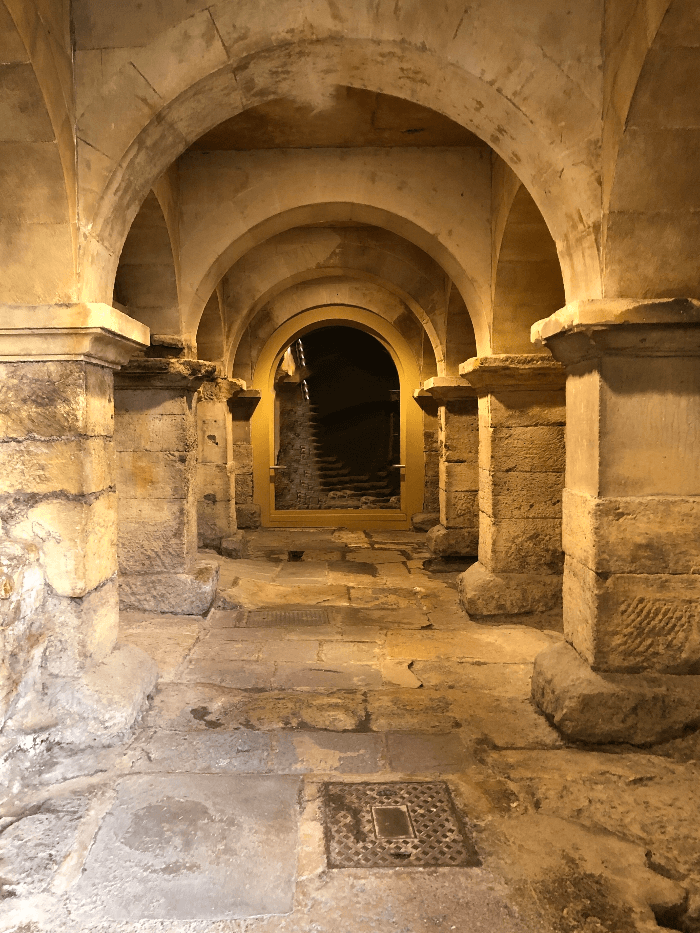 a hallway with a stone floor and stone arches