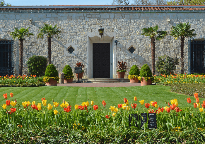 a white Spanish-style house with red and yellow flowers in the beds
