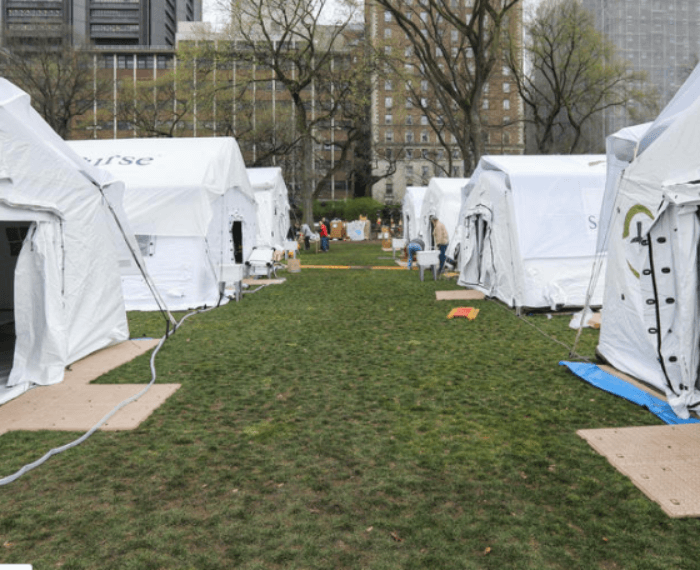 a row of white tents in green grass
