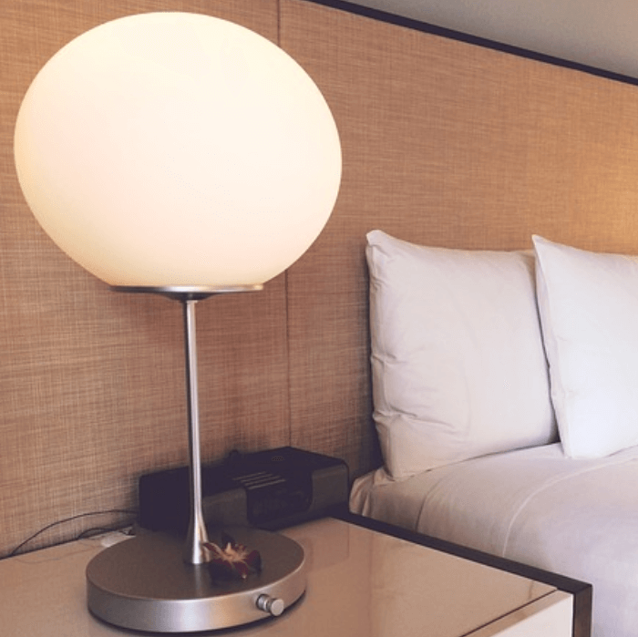 a bed side table lamp in a hotel room
