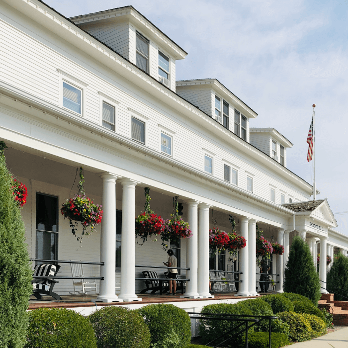 white building with columns and bright flower baskets