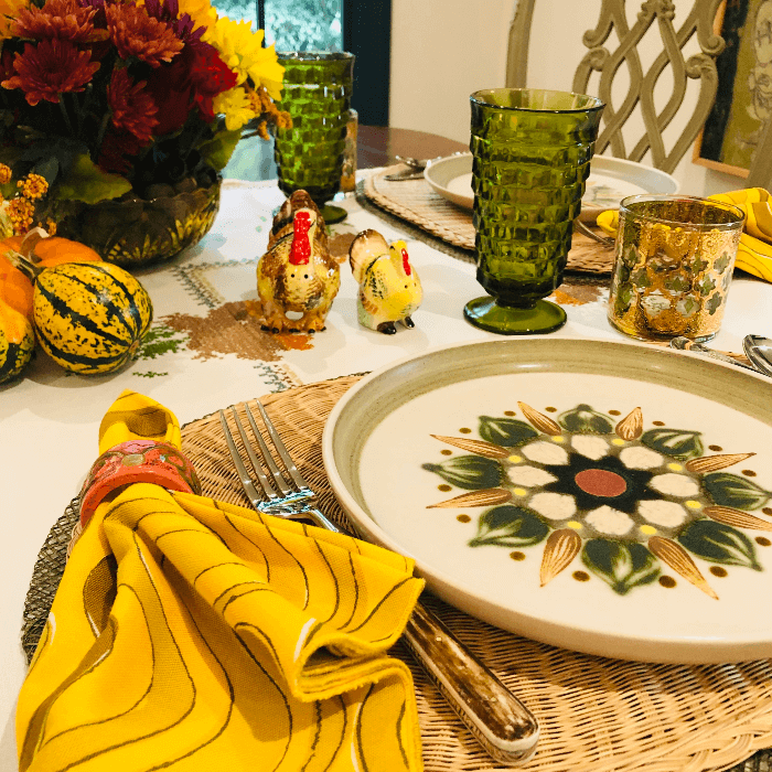 a table decorated with green glasses and yellow napkins
