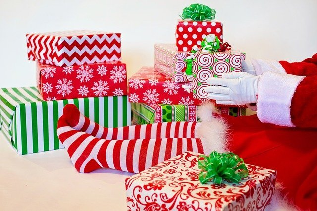 a pair of legs in red and white socks surrounded by red and green presents