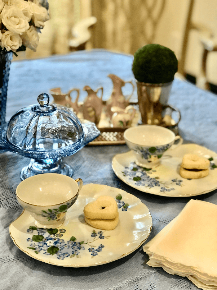 Small white plates with tea cups and cookies