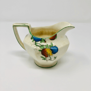 a small white pitcher decorated with red and blue fruit