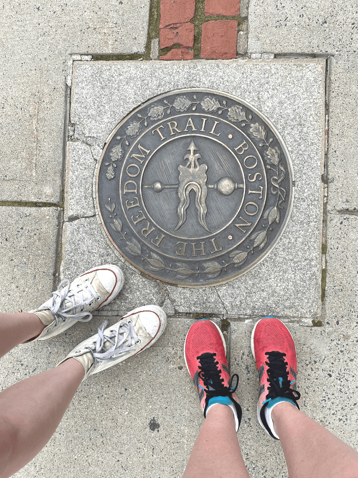 Two pair of feet standing on a Freedom Trail Marker