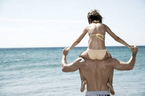 A father's love for his daughter: Girl (8-10) on father's shoulders by sea, rear view
