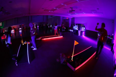 Students play miniature golf, one of the many games offered at the Silent Disco party. | Photo by Justin Tijiera/The Cougar.