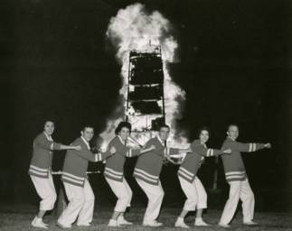 Cheerleaders make a line in front of a lit bonfire.   Courtesy of UH