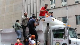 Parade attendees at the corner of Walker and Milam board a dump truck after it worked its way through the crowd and stopped 50 feet before the intersection barricades. | Thomas Dwyer/The Cougar