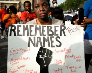 An unidentified demonstrator holds a poster with the names of Floyd and some others who died in police-related altercations in the United States. | Mikol Kindle Jr./The Cougar