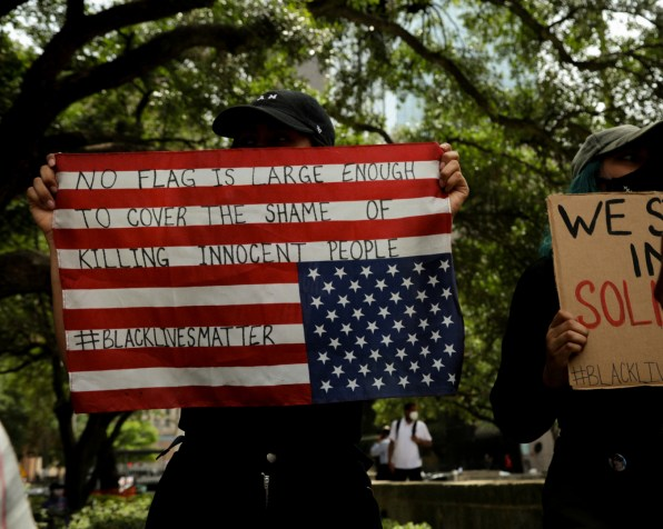 """A protester holds an American flag upside down with the words, """"No flag is large enough to cover the shame of killing innocent people,"""" sprawled across it. Under it is the hashtag of the Black Lives Matter movement, which has become integral in the protests. 