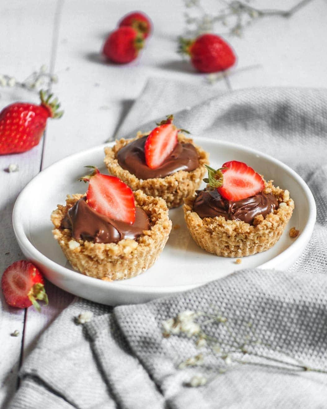 De minis tartelettes garnies de pâte à tartiner au chocolat et noisettes ainsi que de fraises
