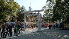The reverse view from the main shrine. In the area in front of the entrance, various street vendors are present, on the occasion of Ume matsuri.