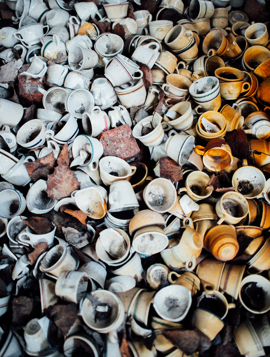 a massive pile of broken mugs in an abandoned factory