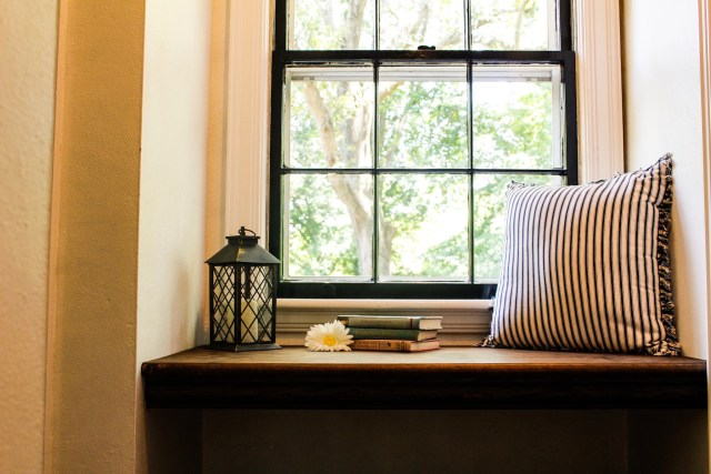 Walnut stain adds depth of color to the new window seat, which is surrounded by white walls and flanked by a paned window looking out at a huge, leafy tree.