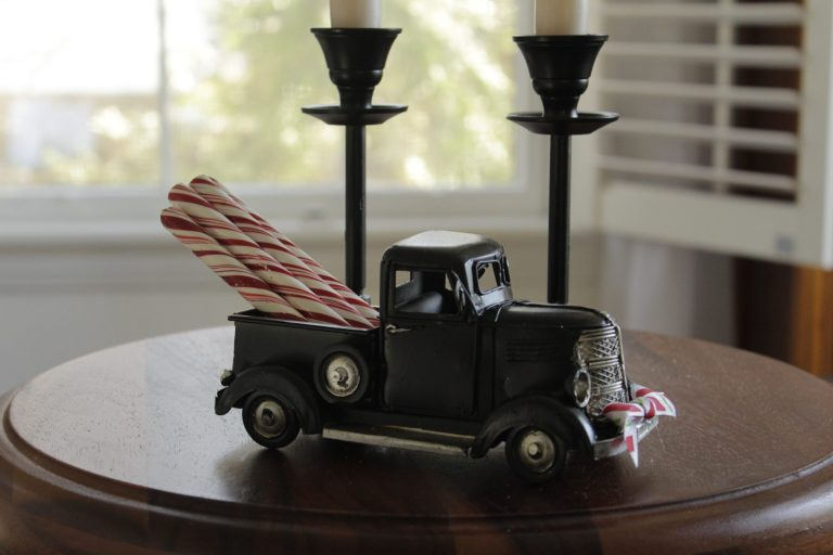 a toy truck that has candy canes sticking out of the truck bed perched on a table with two candlesticks in the background