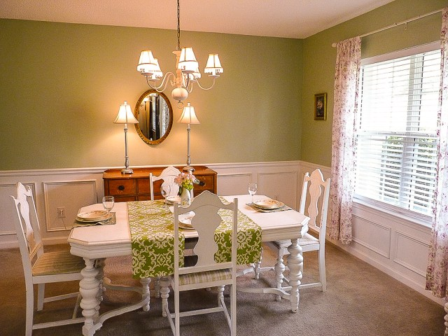 Dining room with green walls and white table and chairs set