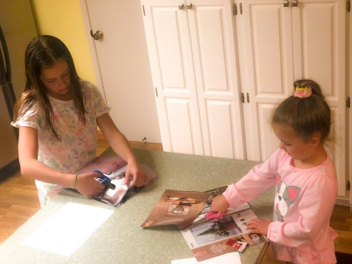 little girls cutting pictures out of magazines