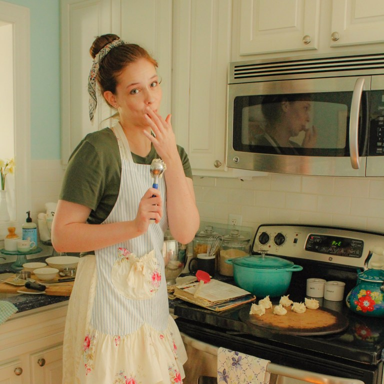 girl baking cookies, licking the spoon