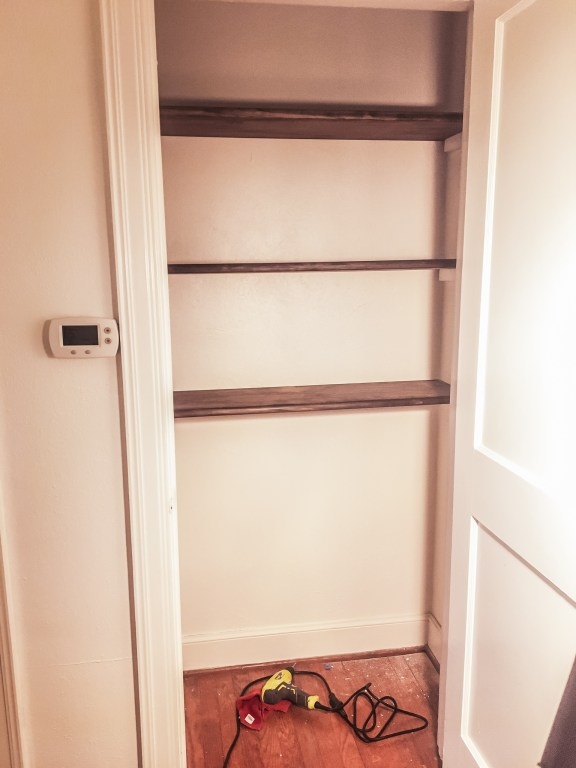 Newly-installed stained-wood shelves in a white-painted closet