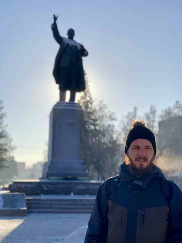 Man standing in front of Lenin Monument Ulitsa Lenina, Irkutsk in the sunshine