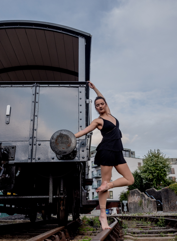 Dancing Circus Traveller posing on a train track