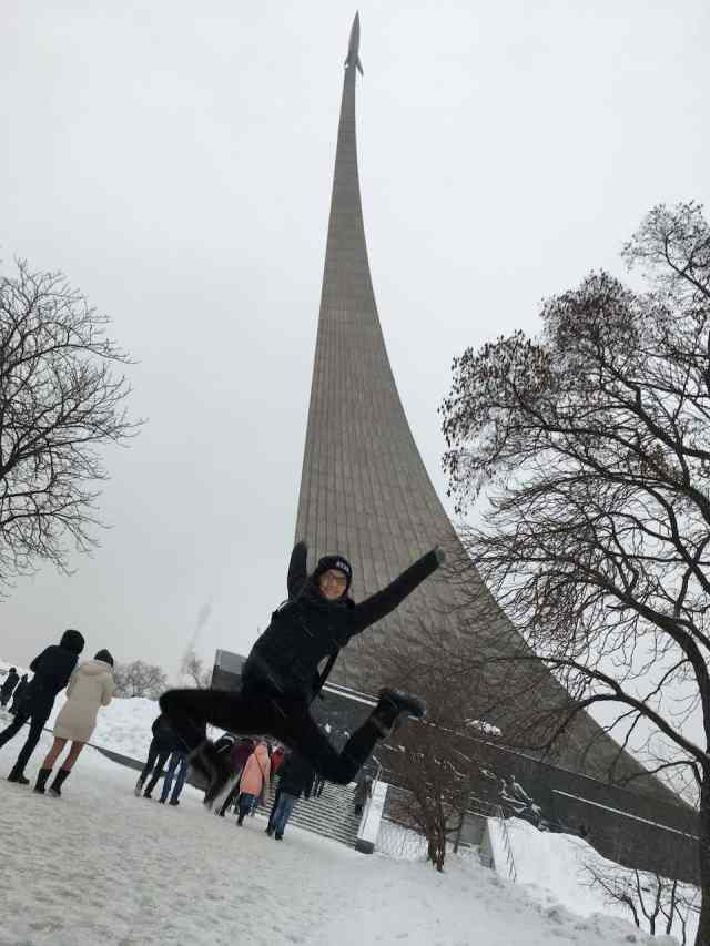 Girl jumping in front of Museum of Cosmonautics Moscow