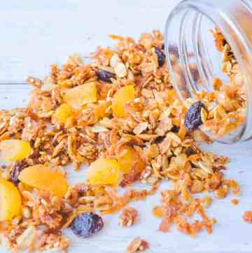 Clear mason jar on its side with fruit and nut granola spilling out onto white wood counter