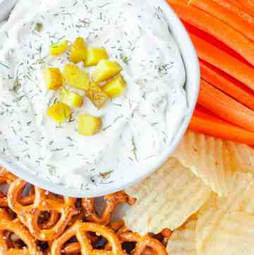 Dill Pickle Dip in a white bowl next to pretzels, potato chips and carrot sticks