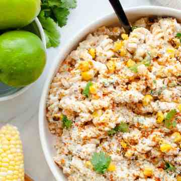 Mexican Street Corn Pasta Salad in a white bowl alongside whole limes and corn on the cob