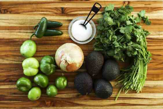 Fresh vegetables, tomatillos, avocados, onion, jalapeno, cilantro sit on a wooden cutting board.