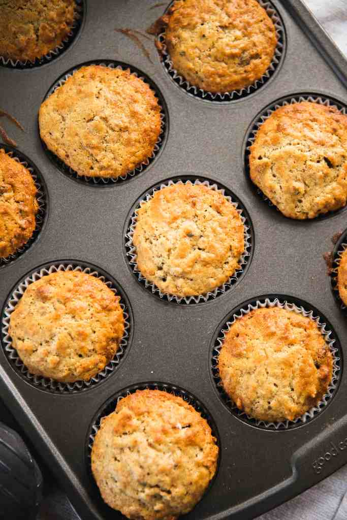 Golden bran muffins sit in a muffin tin, fresh out of the oven.