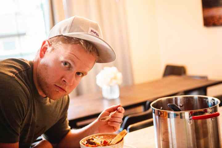 Dallin, a middle age man, looks at camera with spoon in hand with a look of surprise on his face. He leans over a bowl of sweet and spicy chili.