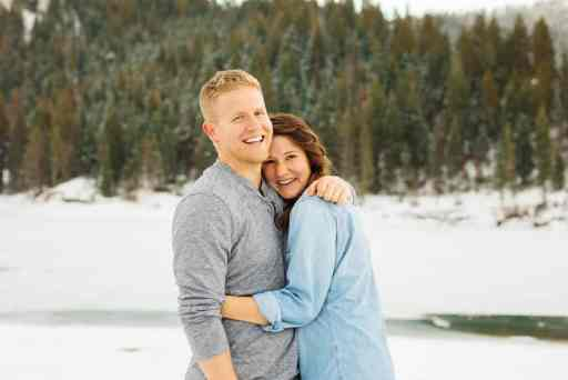 Dallin and Ashley from the Dashley's Kitchen, stand hugging in front of a line of trees with snow on the ground.