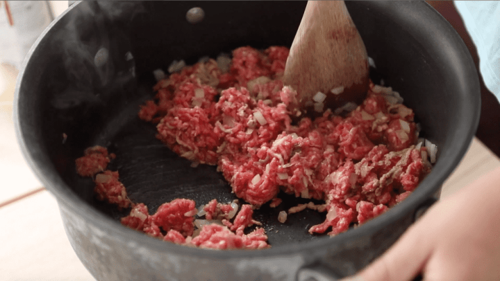 In the large pan uncooked ground beef is being mixed in with the sautéed onions.