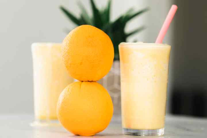 Orange Julius Smoothie in a glass ready to drink. Two oranges stacked on the left of the glass.