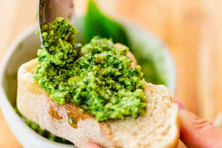 Freshly made pesto sauce is being spooned onto a thick slice of bread.