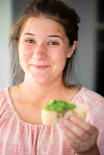 Ashley smiles while holding a thick slice of bread topped with fresh homemade pesto.
