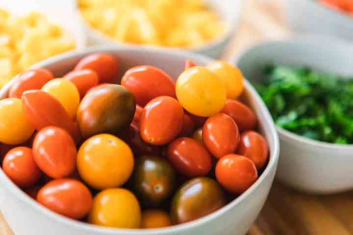 In a bowl sits ripened cherry tomatoes, red, dark greens and yellows.