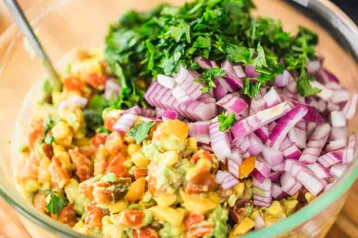 Salsa sits in a bowl with fresh chopped cilantro and diced red onion on top, ready to be mixed in.