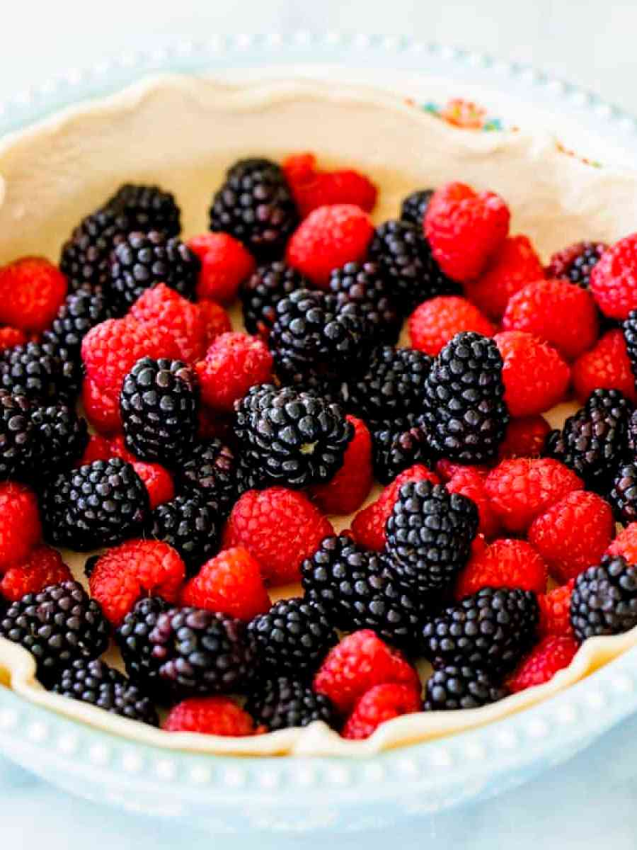 A simple egg blue pie tin is lined with a pie crust and filled with vibrant mixed raspberries and blackberries.