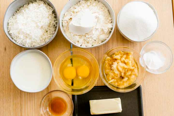 Ingredients for banana cake sit on the counter shredded coconut, flour, salt, sugar, soured milk, eggs, mashed bananas, vanilla and butter.